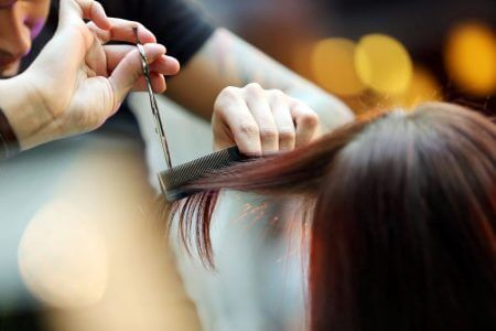 hairdresser trimming blond hair with scissors